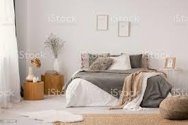blumen auf hölzernen stuhl und hocker in weiße schlafzimmer innenraum mit plakaten über bett echtes foto stockfoto und mehr bilder beige