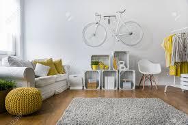 modernes wohnzimmer mit sofa teppich holzplatten und fahrrad an der wand hängen