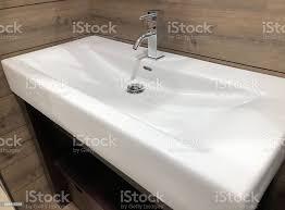 granit waschtisch über hölzerne schrank und weißen rechteckigen eitelkeitswanne mit chromarmatur stockfoto und mehr bilder badezimmer