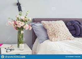 gemütliches schlafzimmer mit blumen auf dem nightstand