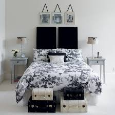 White Guest Bedroom With Double Bed Raised Headboard Floral Bedding And Storage Boxes