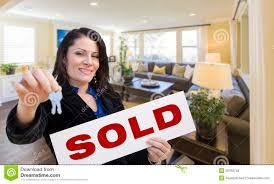Hispanic Realtor With Keys And Sold Sign In Living Room