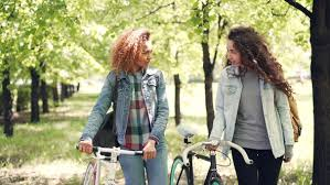 Dolly Shot Of Cheerful Girls Friends Walking In Park With Bikes