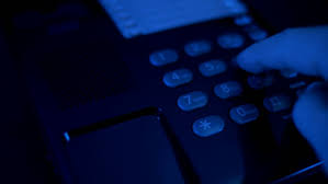 In the dim lights hand picks up the black phone dials a number and hangs