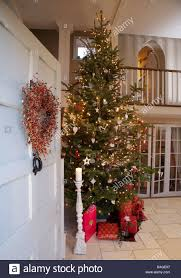 Wreath On Open Front Door With View Of Tall Christmas Tree And Gift Wrapped Presents In
