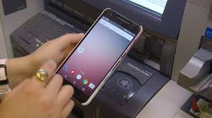 Hands on NFC enabled ATMs make it easy to withdraw cash with a