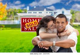 Young Happy Hispanic Couple In Front Of Their New Home And Sold For Sale Real