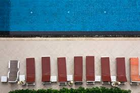 Swimming Pool With Long Chairs Set On Top View In The Hotel Stock Photo