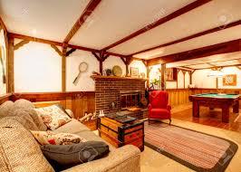 gemütliches wohnzimmer mit deckenbalken rustikale teppich holz getäfelten wände gesteinigt hintergrund kamin und billardtisch
