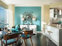 A Turquoise Accent Wall With An Oversized Sunburst Mirror Is The Focal Point Of This Tropical Midcentury Apartment Design By Gacek Group