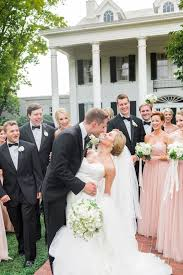 Groomsmen In Black Tuxedos And Bridesmaids Blush Gowns