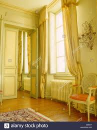 Silk Drapes On Tall Windows In Opulent French Chateau Dining Room With Painted Balloon Back Chair And Double Doors