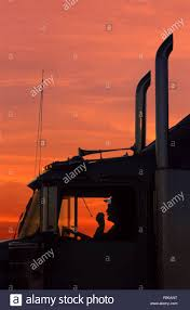 100 Class A Truck Driver Shiloiuette Of A Truck Driver On His CB Radio In The Cab Of His