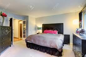 master schlafzimmer mit schwarzen möbeln set und teppichboden doppelbett mit schwarzem kopf bord und beige bettwäsche