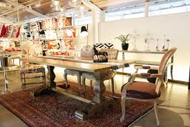 A Wooden Dining Table With White Wall Along Hanging Lights