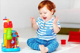 la maison du jouet petit bébé roux heureux jouant avec la maison de jouet photo stock