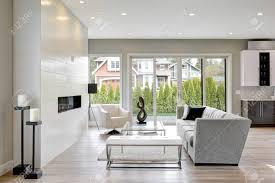 wohnzimmer im modernen stil mit modernem gaskamin holzboden und glastüren umgeben grauen wänden führen auf die terrasse hinaus nordwesten usa