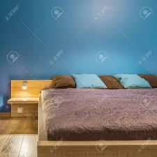 neues blaues schlafzimmer mit bequemen hölzernen großen bett mit braunen und blauen kissen