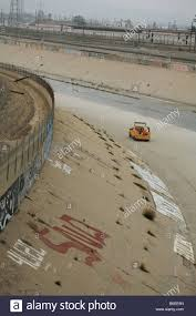 Yellow Truck Driving In The Los Angeles River Bed With Graffiti And ...