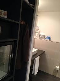 links der offene kleiderschrankund daneben der kühlschrank