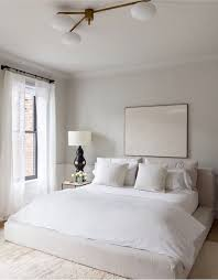 white neutral bedding with khaki fabric upholstered