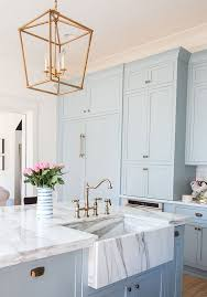 Serenity Blue Kitchen Cabinets With White Marble Countertops And Brass Touches For A Retro Look