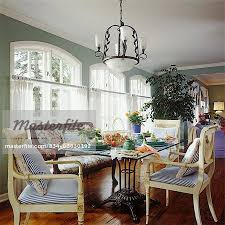DINING ROOM Large Arched Windows Floral Settee White Empire Style Chairs Glass Table With Iron Base Wood Floors Ring Top Pinch Pleat Curtains