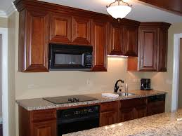 cherry cabinets black appliances the warm tones of these cherry