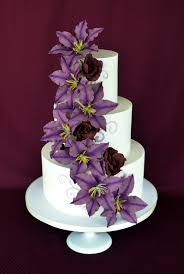 White Wedding Cake With Cascading Sugar Clematis In Purple And Black Magic Roses