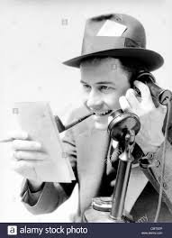 1930s MAN EXCITED NEWSPAPER REPORTER SMOKING PIPE PRESS PASS IN HAT TALKING ON UPRIGHT PHONE REPORTING