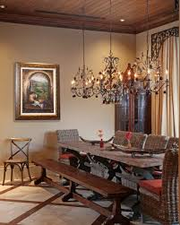 Dining Room Using Three Hanging Wrought Iron Chandeliers Over Wooden Table With Parsons Rattan Chairs And A Bench