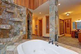luxuriöses herrenhaus badezimmer mit einer drop in badewanne die mit steinfliesen verkleidet ist natürlichen steinsäulen einer beeindruckenden