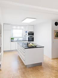 moderne weiße küche mit edelstahlgriffen kochinsel mit