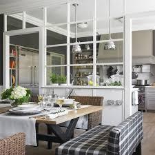 cuisine et maison une verrière de bois blanc délimitant la cuisine et la salle à