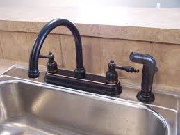black bronze kitchen faucets with stainless steel sink in the