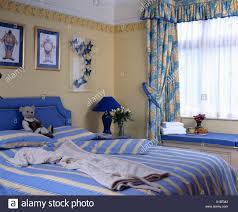 blau gemusterte vorhänge und gestreifte bettwäsche im gelben