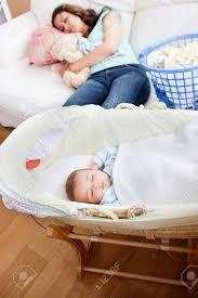 junge mutter schlafen auf dem sofa während ihr baby in seine wiege in wohnzimmer schläft