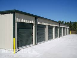 Steel Mini Self Storage Tan Building With Green Trim Roll Up Doors
