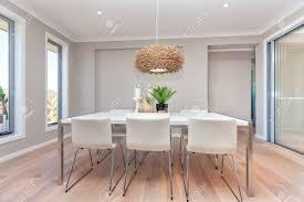 luxus esszimmer und eine helle farbe holzboden und graue wände mit zwei fenstern rund um den bereich mit ausnahme der rechten seite glastür und zugang