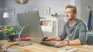 porträt hübscher mann arbeiten am pc sitzend an seinem schreibtisch im hintergrund stilvolle gemütliche wohnzimmer junge freier mitarbeiter
