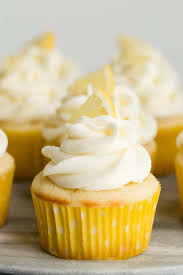 Lemon Cupcakes Topped With Frosting And A Tiny Piece On Top
