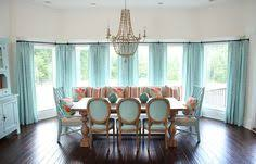 A Light Beachy Vibe Penetrates This Dining Space Thanks To An Expanse Of Large Windows And Abundance Aqua Furnishings Beautiful Chandelier Dresses
