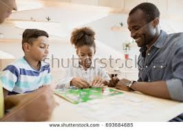 African American Family Playing Board Game In Cafe