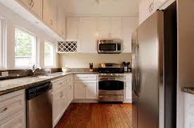 Classic And Antique White Kitchen Cabinets With Stainless Steel Appliances Brown Wooden Floor