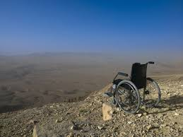 An Empty Wheelchair Sits On The Edge Of A Clifflooking Out