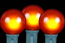 orange g50 globe outdoor string light set on green wire