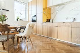 stilvolle und gemütliche skandinavische esszimmer und küche mit designfamilietisch stühlen und le weiß und marmorwänden und braune holzparkett