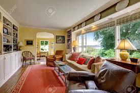 wohnzimmer mit weißen schränken braunen möbeln und roten teppich
