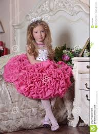 young princess in an elegant pink dress sitting stock photo