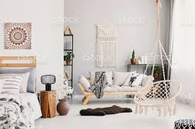 helles wohnzimmer interieur mit makramee an der wand beige mit kissen und decke hängestuhl flauschigen teppich und nachttisch mit le stehen
